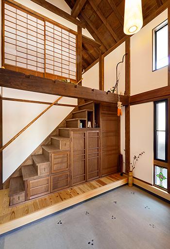 【玄関】「玄関は広くしたい」という夫の希望で、吹抜けと土間を設けた。階段は箱階段のような趣を出し、収納を確保しました