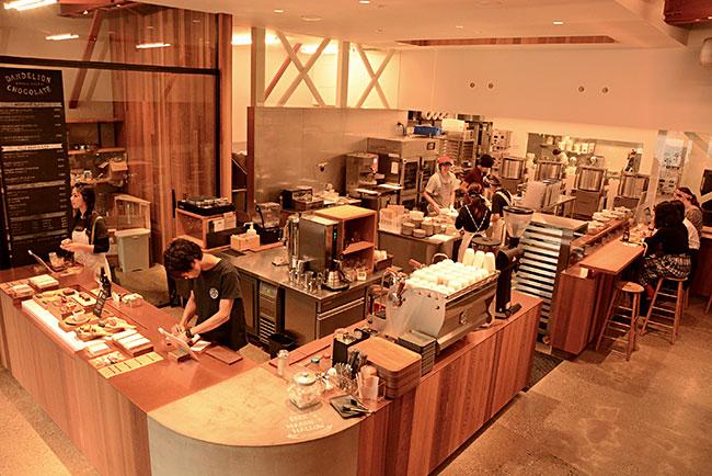 天井が高く、柱の少ない元倉庫は、広いスペースを必要とするチョコレートづくりにうってつけ。二階はカフェスペースとなっていて、若者だけでなく、地元のお年寄りから、子連れファミリーまで、さまざまなお客でにぎわっている