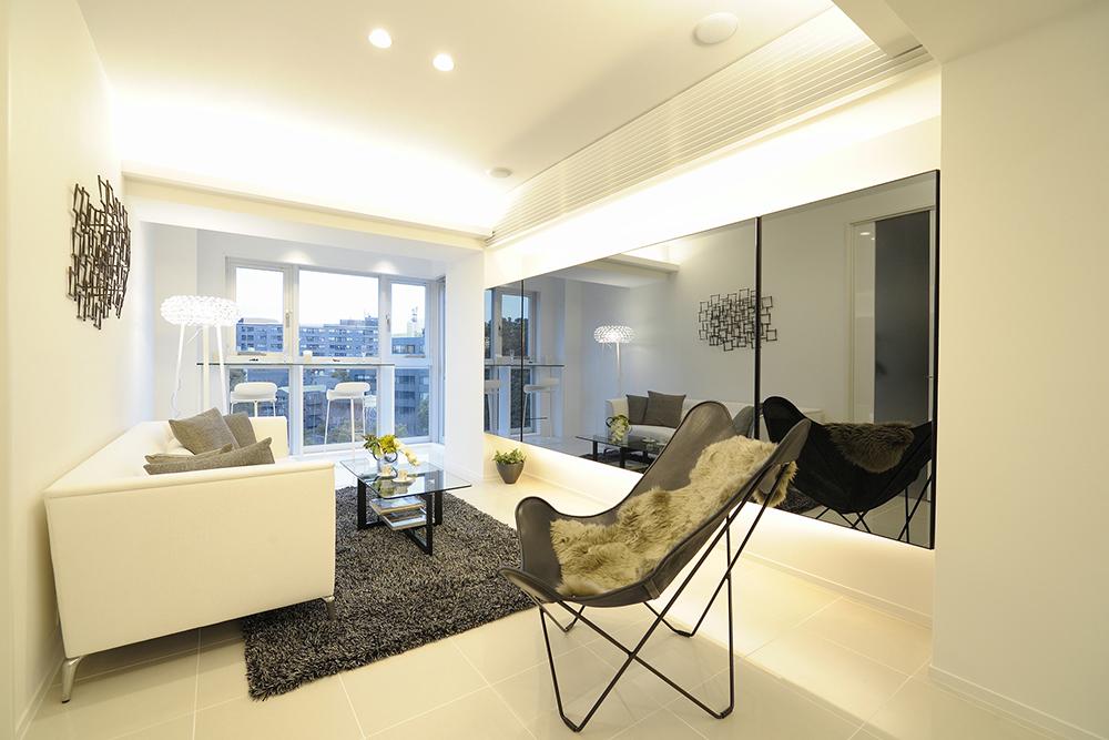 白い壁にブラックやグレーのインテリアが映えるシンプルモダンな部屋の写真