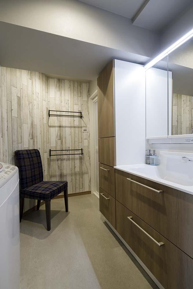 洗面台の扉に合わせた木目柄の壁紙