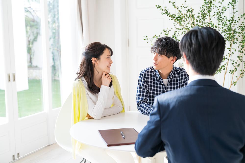 若い夫婦と不動産会社の営業担当者のイメージ写真