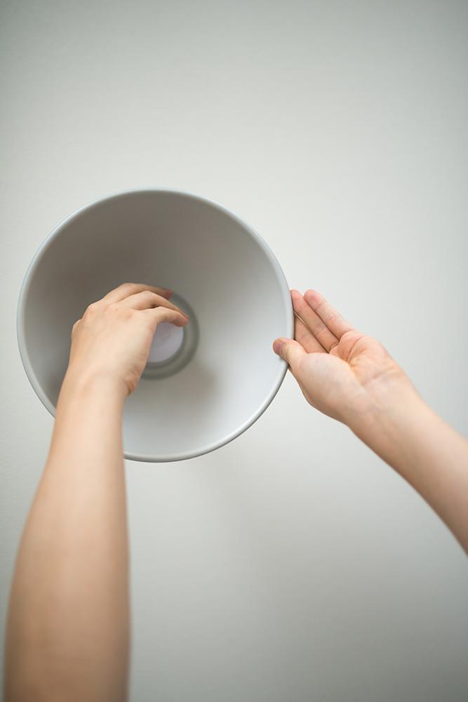 天井に設置するタイプの照明器具の電球を変えている写真