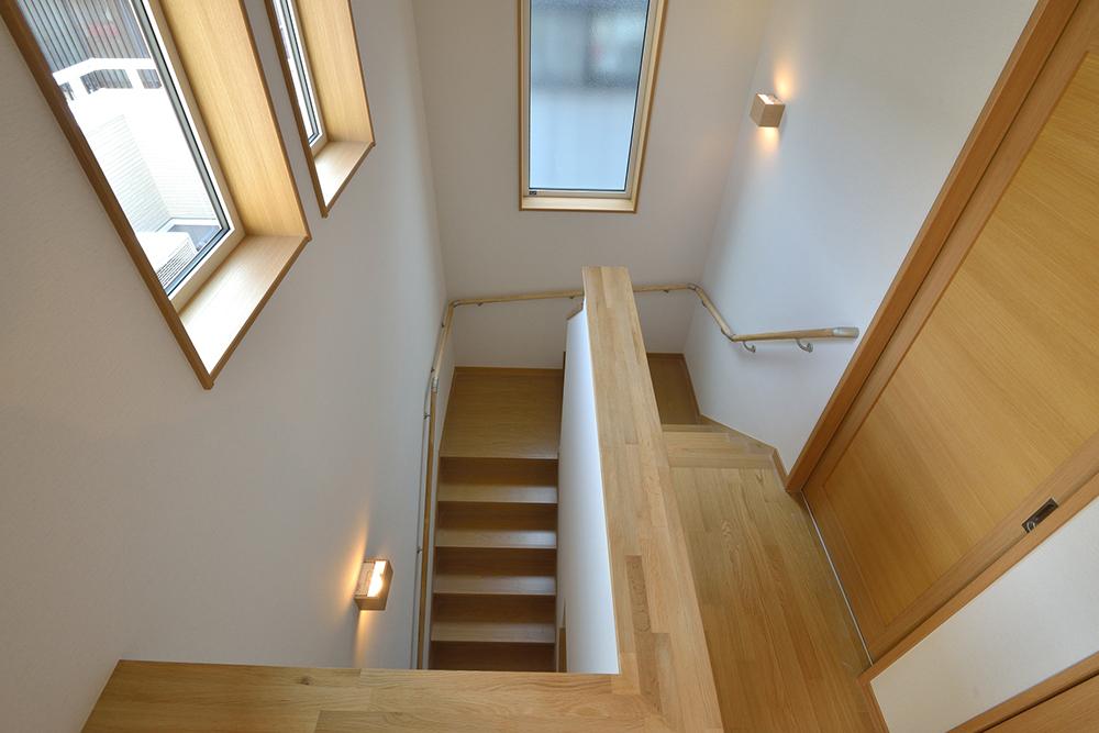 折り返し階段の最初と最後の壁面に一つずつ照明を設けている