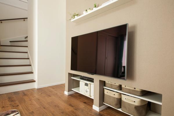 壁がけのテレビの下に、収納スペースを設けたリビング実例