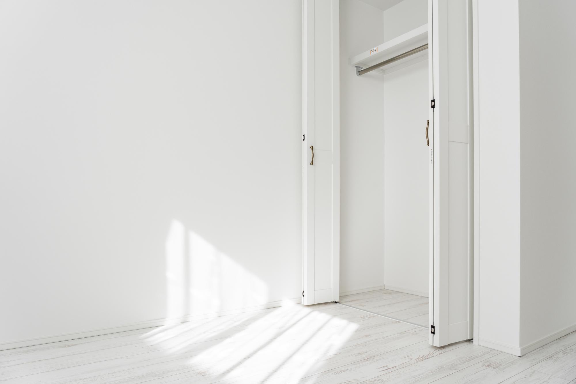 扉が開いたクローゼットの写真