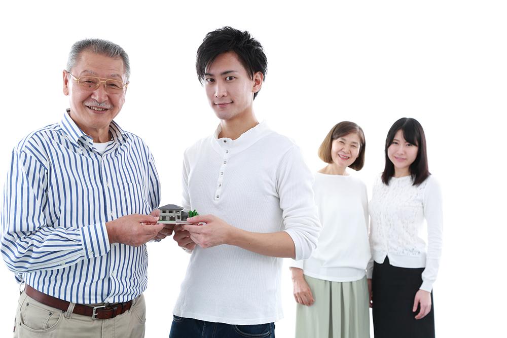 家の模型をもつ2世代家族の写真