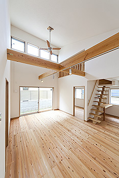 開放感のある勾配天井のリビングとロフトへ上がる固定階段