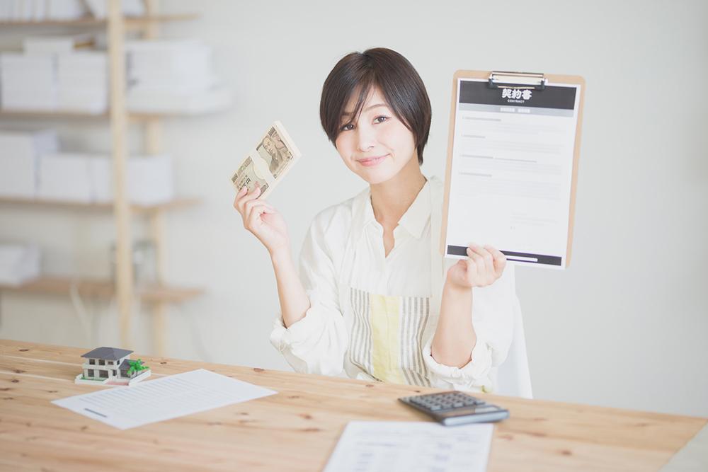 物件の契約書とお金を持つ女性