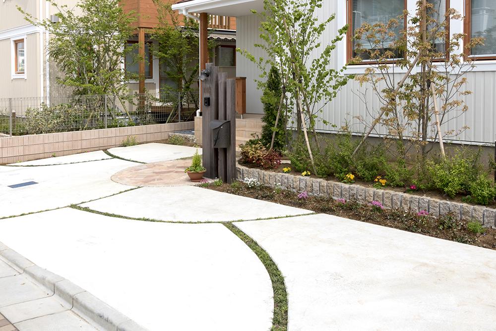 アーチ状のライン部分に芝生を植えて、おしゃれなデザインにしたコンクリートのアプローチ