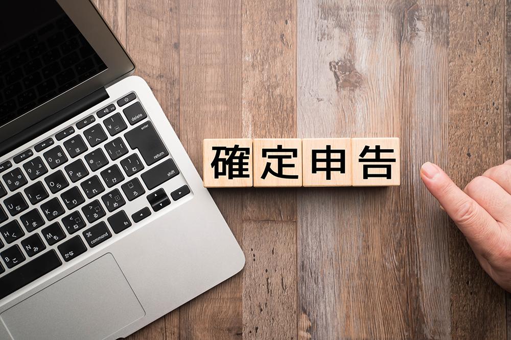 確定申告の文字を指す指とパソコン