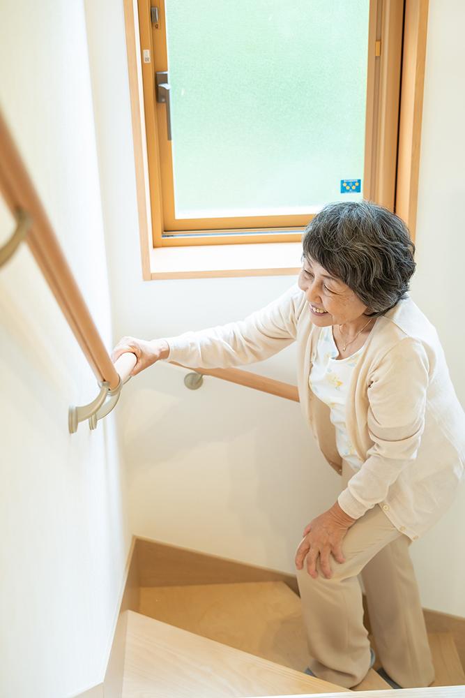 階段の手すりを持って歩くシニア女性