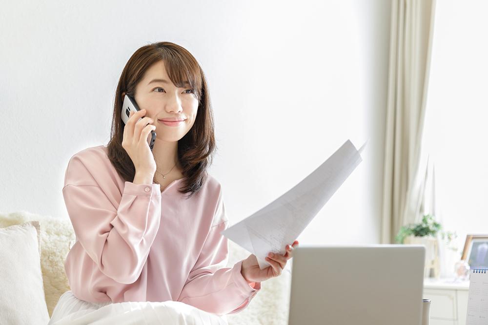 書類手続きについて電話で確認する女性