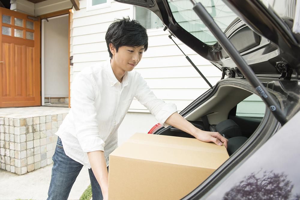 車に荷物を積む男性