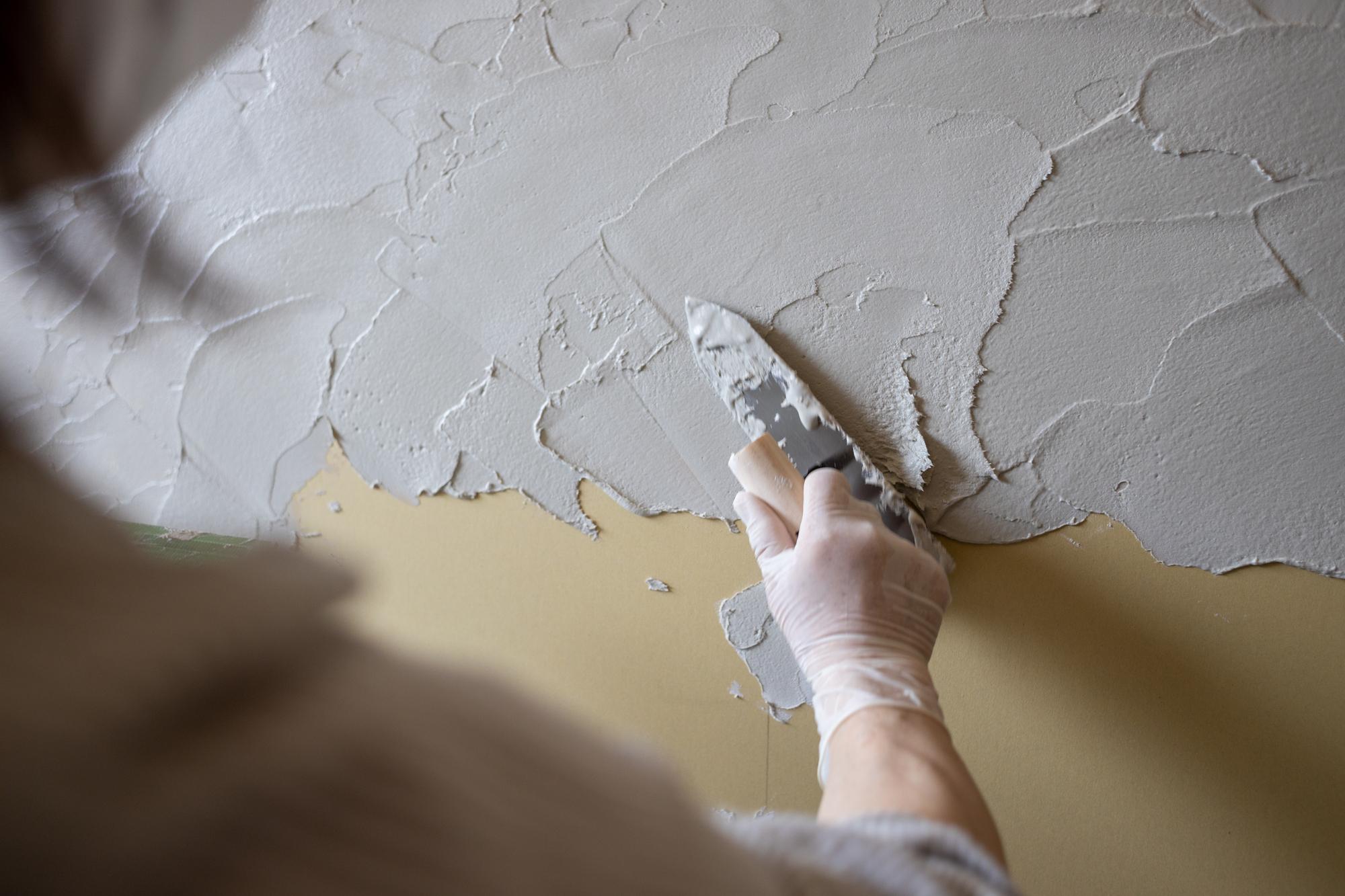 砂壁を手早くコテで均一に塗り広げる