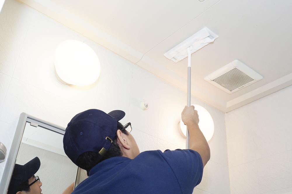 お風呂の天井を掃除する男性