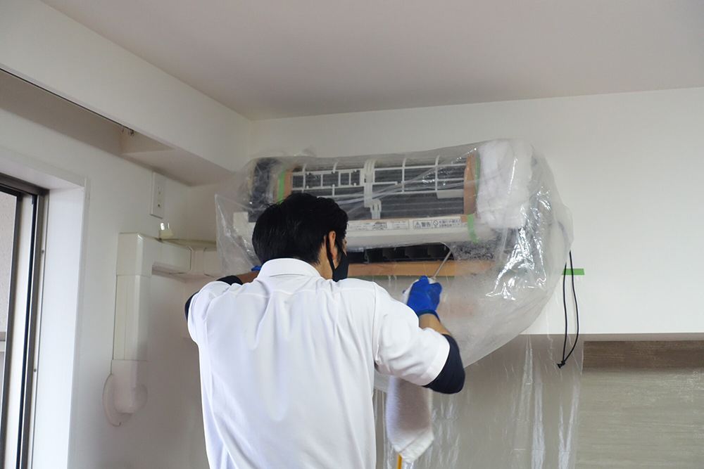 エアコンの掃除をする人の写真