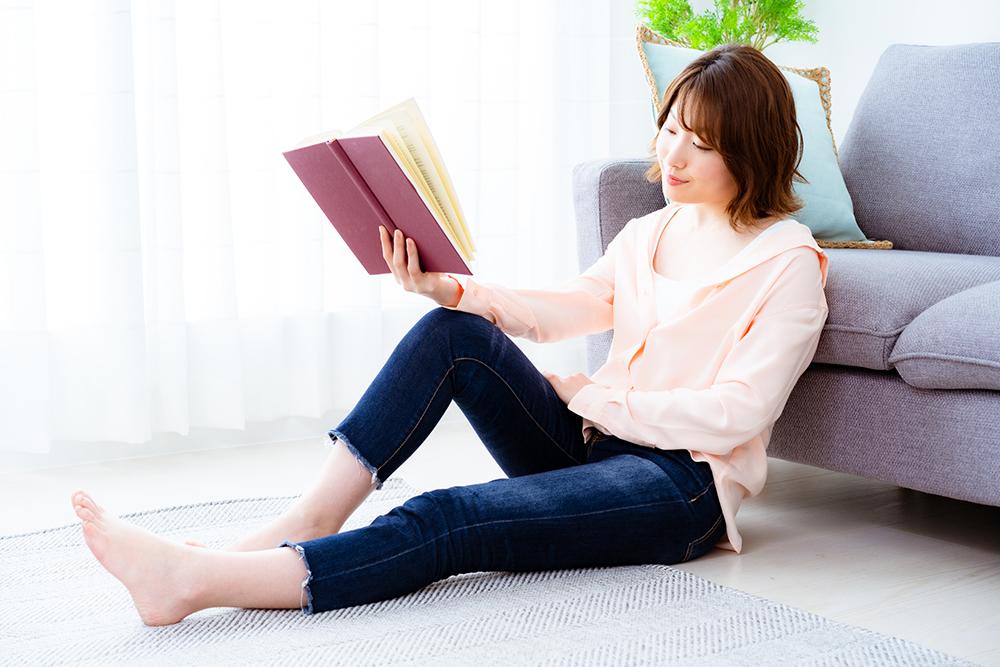 ソファを背もたれにしてカーペットに座る女性