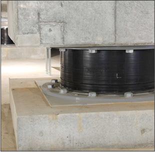 マンションの基礎の部分に設置された免震装置。積層ゴムと呼ばれる素材でできており、地震のエネルギーを吸収して建物に伝わるのを防ぐ(撮影協力/長谷工コーポレーション)