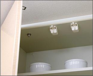 キッチンの吊り戸棚に設置された耐震ラッチ。地震の際に扉が固定され、中の食器が飛び出さない仕組みだ(撮影協力/長谷工コーポレーション)