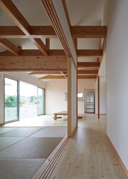 玄関ホールから見た広間。シンプルな面と線の構成や色使いによって、木や琉球畳といった素材の味わいや調和、あらわし梁などの造形の美しさが引き立ち、落ち着きと趣を両立した空間