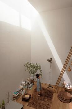 スカイライトから光が降り注ぐ空間。周辺を建物に囲まれて採光が十分に取れない狭小地でも、天井高(吹抜け)を確保し上部に天窓を設けることで、上部から光を招き入れる設計。白い壁は光を反射させるレフ板のような効果があり、北側でも明るさが空間全体に行きわたる。光の表情を追うのも楽しい