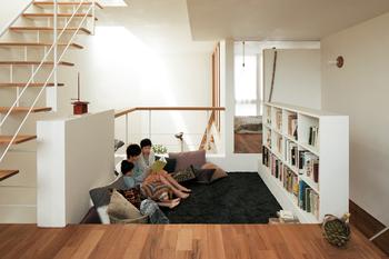 1階と2階をつなぐ吹抜けに、突き出るように浮かぶピットラウンジ。一段下がった床に腰を下ろすと、周囲に開かれる心地よさと、こもるような安心感を同時に味わえる