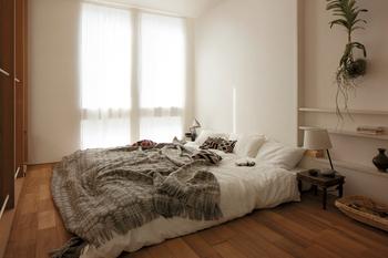 無垢材の床などナチュラルな素材感を大切にしたベッドルーム。ローベッドで空間を広く使いながら、くつろいだ時間を過ごすことができる