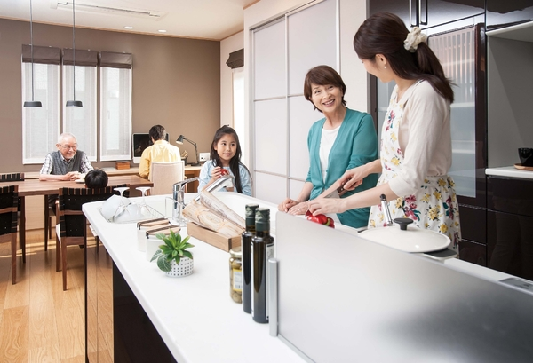 キッチンを中心に大型のワンルーム構成でプランニング。普段はそれぞれのリズムで暮らしながら、親世帯が暮らす1階に集うときには、コートヤードを中心にリビング、ダイニング・キッチン、和室の回遊動線が自然な交流を創出する
