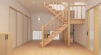 玄関の引戸を開けると、広々としたホールがお客様を迎える。落ち着いた色調のタイルや壁のない開放的な階段が上品なおもてなしの空間を演出する