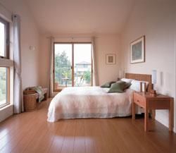 2階の主寝室は勾配天井で開放感いっぱい。バルコニーからは中庭と「マルチコーナー」が見下ろせる。また、居室には熱気がこもらないよう欄間ドアが備えられており、効率的に換気でき、快適に過ごすことができる