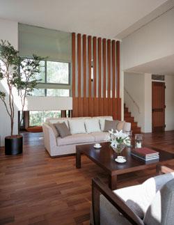 3.4mの高天井で開放感に満ちたリビング。正面に1階蔵とスキップして和室が設けられています。木の縦格子が空間のアクセントに。リビング階段の提案も見所です