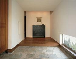 塗り壁の端正な玄関、地窓から光を取り込む設計で、空間の広がりを強調するために天井はあえて低く設計
