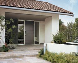 深い軒の出と渋い色合いの屋根瓦が印象的。外壁は塗り壁仕上げ。アプローチの石張りが、美しい佇まいを極立たせます