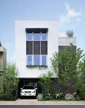 ビルトインガレージを備えた3階建外観。コートを取り囲むようにコの字型に配置され全居室に通風と採光を確保。