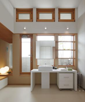 ファミリーライブラリーから半階上がったところが2階の洗面室・バスルーム。約3.1mもの天井高を確保したスペースは、室内干しの場としても最適である。高窓から湿気が抜けていく設計でいつも快適。右手にはリネン類や下着用の衣類の蔵が設けられている