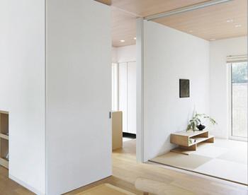 玄関からリビングのドアは天井まである引き戸。開けた状態で壁の一部になるように設計。冬などには閉めてしまうとスッキリとした佇まい