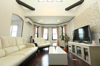 こだわりが詰まったリビングルーム。窓側のゆるやかな多面形状と上下2段のスリット窓が四角いリビングとは違う趣をかもしだしている。吹き抜けから注ぐ陽光で室内は明るく心地よい空間だ