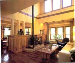 上下の窓から陽光が降り注ぎ、吹き抜けによってのびやかな空間となっているリビング