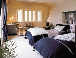 広々とした主寝室の奥には、寝る前に夫婦でグラスを傾けくつろぐスペースがある。右側の階段はマスターズ・ロフトに続く