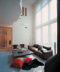 家の中心に位置し、家族が最も集う共有スペースのリビングは、水平方向だけでなく、吹き抜けによって垂直にも大きく空間が広がり、くつろぎと開放感に満ちている。吹き抜けを活かしたダイナミックな3連窓から降り注ぐ陽光があたたかい。