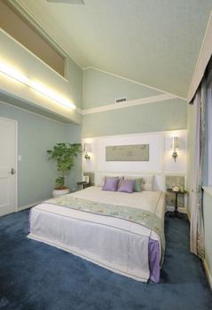 のびやかな勾配天井、ベッドレイアウトに配慮した壁面装飾やブラケット照明。上質なホスピタリティを感じる主寝室。隣接するウォークインクローゼットから、浴室や洗面・洗濯室にもつながる