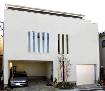 外観バリエーション例 1:スリット窓の連なりがデザインのクオリティを高めている外観。左手には車2台を楽々収納できる大開口のビルトインガレージを設けた(東京都 F様邸外観写真)