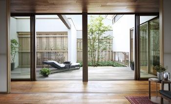 """暖かな光に包まれる中庭を通して、住まいの全貌が見渡せる。ダイニング、リビング、個室、ガレージ。そんな横への広がりが、この平屋を誰もがうらやむような邸宅にする。すべての部屋とつながる、わが家の中心「インナーコート」。ここは、住まいに守られながら、""""外""""で優雅に過ごせる""""内""""空間でもある"""