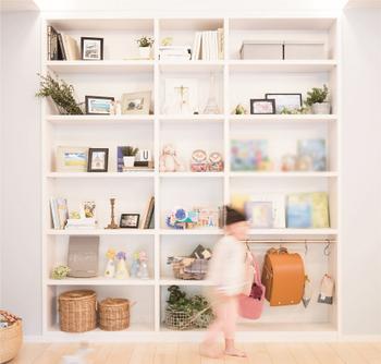 共有スペースに本棚を設置。家族の写真やこどもの作品を飾れる「見せる収納」でギャラリー空間に