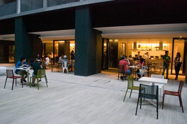 【画像1】商業施設のお洒落なテラス、といった雰囲気の中庭。奥にはキッチンダイニングがあり、入居者同士が仲良く料理をつくっていました(写真撮影:榎並紀行)