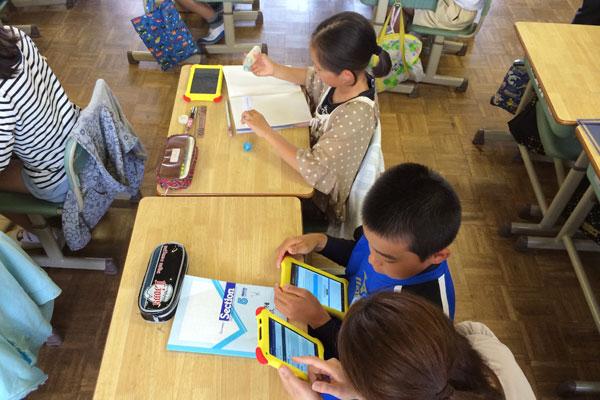 【画像1】小学生全員に持ち帰りが前提のタブレットを貸与した。ノートや鉛筆と同じく、学習の道具としてタブレットを活用している。反転授業で用いる以外にも、屋外に持ち出して花や植物の写真を撮って、その名前を調べたり、学習へ多様な利用を行う(写真提供:武雄市)
