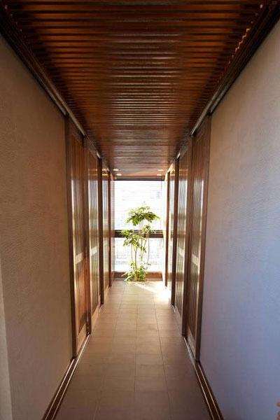 【画像9】玄関を開けると正面の窓から外の景色が飛び込んでくる。各部屋への入り口は一番奥にあり、扉を閉めていても土間を行き来する人の気配を感じられる(写真撮影:筆者)