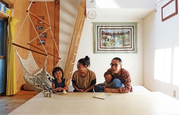 町上貴也さん(33)、広子さん(32)、長女(4)、長男(1)。インドから持ち帰った大きなハンモックがリビングに(写真撮影:倉畑桐子)
