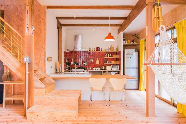 【画像3】〈AFTER〉西向きの対面キッチンは、赤いタイルがアクセント。料理をしながらスキップフロアで遊ぶ子どもたちが見渡せる、広子さんお気に入りの場所(画像提供/リノキューブ)
