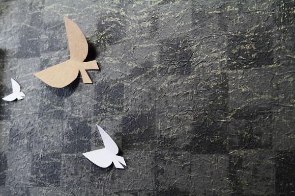 【画像1】黒とチャコールグレーの格子模様のうえに、ゴールドが散りばめられたデザインが特徴の壁紙。壁から羽ばたき出しているかのように、蝶の切り絵を壁にピンで留めている(写真撮影:藤本和成)